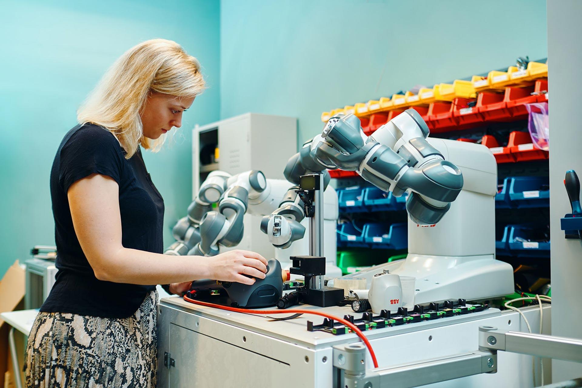 Medarbetare på Robotdalen i Västerås jobbar med en ABBs robotar. Foto: Pressbild