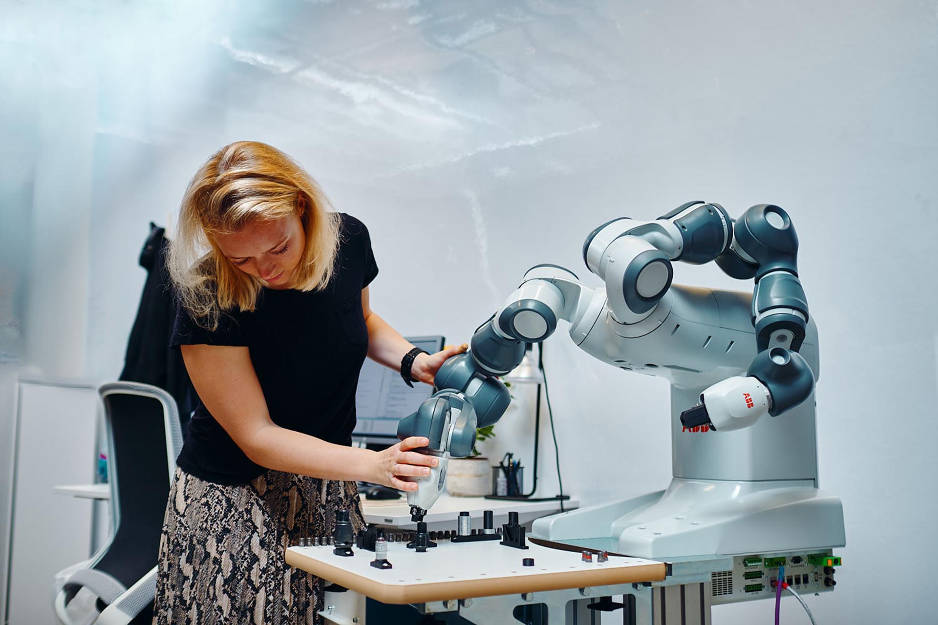 En medarbetare på Robotdalen i Västerås jobbar med en av ABBs robotar. Foto: Pressbild